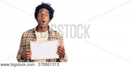 Handsome african american man with afro hair holding blank empty banner scared and amazed with open mouth for surprise, disbelief face