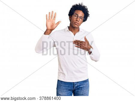 Handsome african american man with afro hair wearing casual clothes and glasses swearing with hand on chest and open palm, making a loyalty promise oath