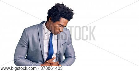 Handsome african american man with afro hair wearing business jacket with hand on stomach because indigestion, painful illness feeling unwell. ache concept.