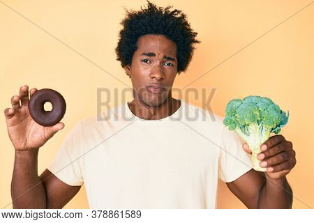 Handsome african american man with afro hair holding broccoli and chocolate donut clueless and confused expression. doubt concept.