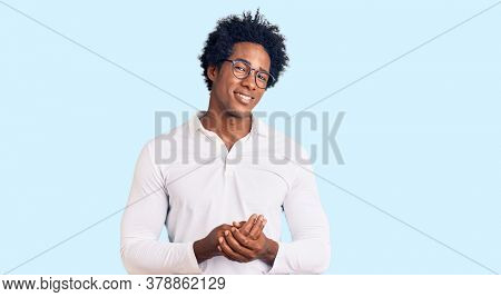 Handsome african american man with afro hair wearing casual clothes and glasses with hands together and crossed fingers smiling relaxed and cheerful. success and optimistic