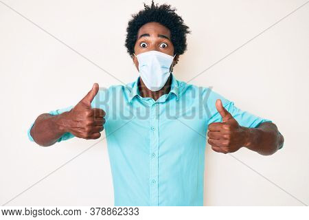 Handsome african american man with afro hair wearing medical mask afraid and shocked with surprise and amazed expression, fear and excited face.