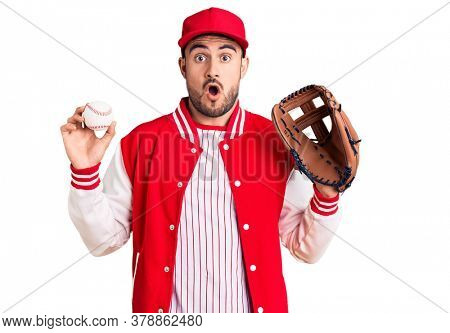 Young handsome man holding baseball gloves scared and amazed with open mouth for surprise, disbelief face