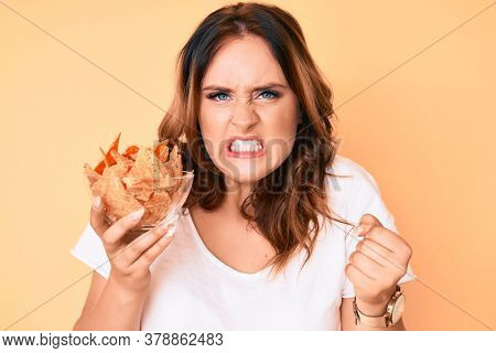 Young beautiful caucasian woman holding nachos potato chips annoyed and frustrated shouting with anger, yelling crazy with anger and hand raised