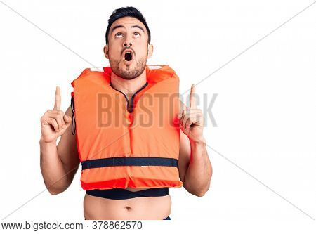 Young handsome man wearing lifejacket amazed and surprised looking up and pointing with fingers and raised arms.