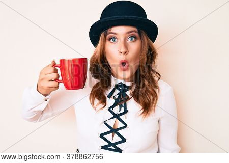 Young beautiful caucasian woman wearing hat and drinking a cup of coffee scared and amazed with open mouth for surprise, disbelief face