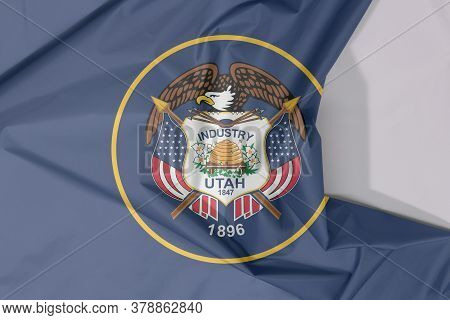 Utah Fabric Flag Crepe And Crease With White Space. The Seal Of Utah Encircled In A Golden Circle On