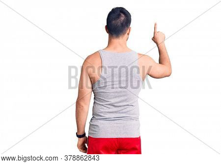 Young handsome man wearing swimwear and sleeveless t-shirt posing backwards pointing ahead with finger hand