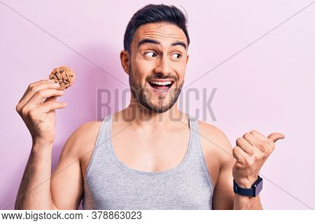 Young handsome man with beard wearing sleeveless t-shirt eating chocolate cookie pointing thumb up to the side smiling happy with open mouth