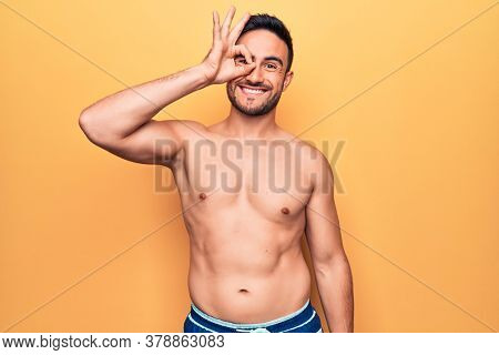 Young handsome man with beard wearing sleeveless t-shirt standing over yellow background smiling happy doing ok sign with hand on eye looking through fingers