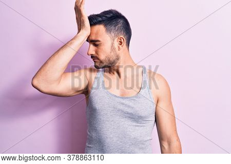 Young handsome man with beard wearing casual sleeveless t-shirt over pink background surprised with hand on head for mistake, remember error. Forgot, bad memory concept.