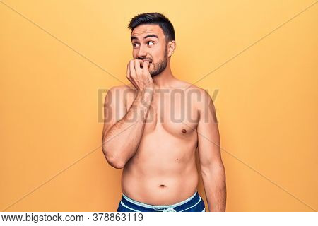 Young handsome man with beard wearing sleeveless t-shirt standing over yellow background looking stressed and nervous with hands on mouth biting nails. Anxiety problem.