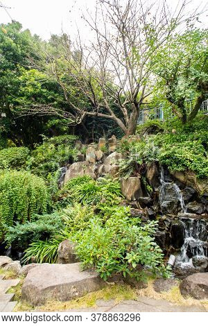 Glover Garden In Nagasaki, Japan, With Green Plants And Trees Formations On The Rock, Small Waterfal