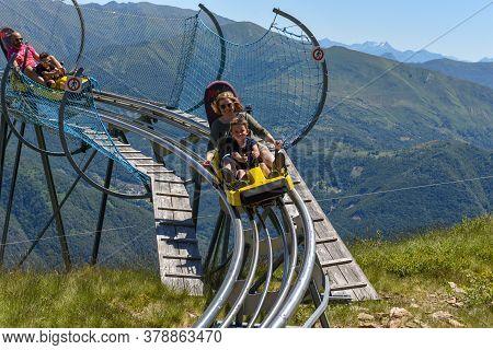 People Tobogganing On The Track Of Mount Tamaro On Switzerland