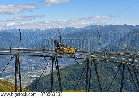 Boy Tobogganing On The Track Of Mount Tamaro In Switzerland
