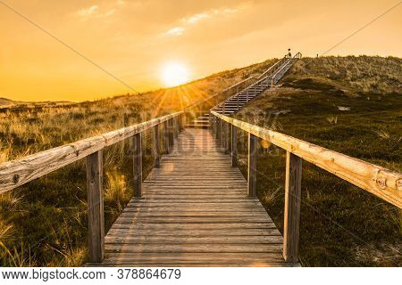 Sylt Island Sunrise Scenery With Wooden Stairs Climbing The Sand Dune. Wooden Deck Over The Covered