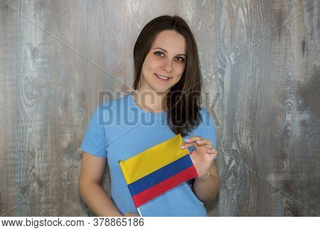 A Young Smiling Woman With A Colombia Flag In Her Hand. Immigration And The Study Of Foreign Languag
