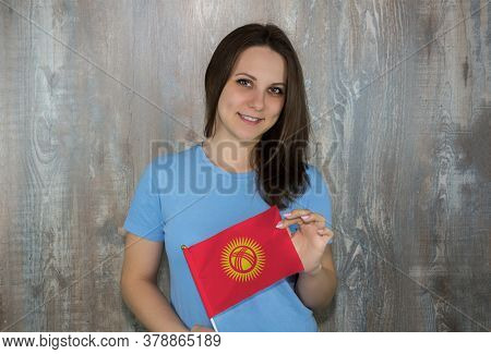 A Young Smiling Woman With A Kyrgyzstan Flag In Her Hand. Immigration And The Study Of Foreign Langu