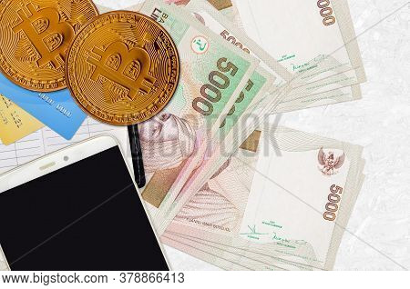 5000 Indonesian Rupiah Bills And Golden Bitcoins With Smartphone And Credit Cards. Cryptocurrency In