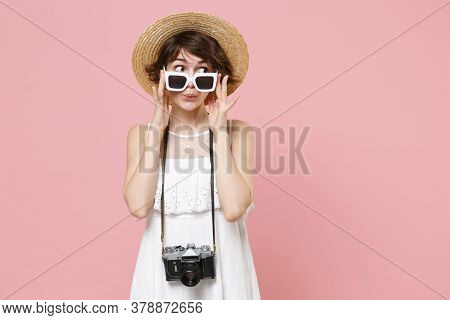 Amazed Young Tourist Woman In Summer Dress Hat Sunglasses With Photo Camera Isolated On Pink Wall Ba