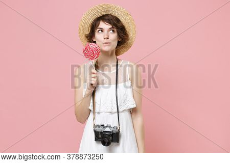 Pensive Young Tourist Woman In Summer Dress Hat With Photo Camera Isolated On Pink Background In Stu