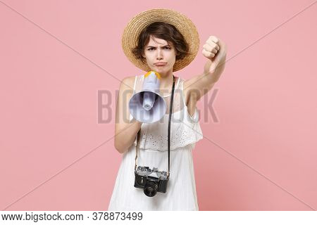 Displeased Young Tourist Woman In Dress Hat With Photo Camera Isolated On Pink Background. Traveling