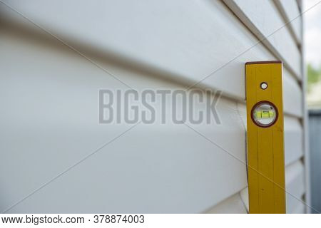 Suburban And Cottage Construction. A Yellow Level Meter Is Attached To A Siding Wall Of A House. Mea