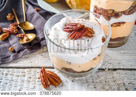 Autumn Trifle Dessert. Layered Pumpkin Pie And Pecan Nut Dessert In A Glass, With Autumn Decorations