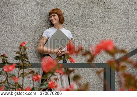 Portrait Of Beautiful Cheerful Woman With Laptop Laughing On City Street