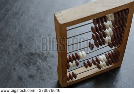 Close-up Old Wooden Abacus On A Black Table. An Obsolete Tool For Mathematical Calculations. Working