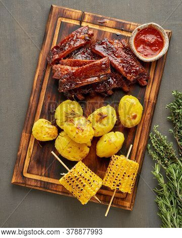 Barbecue Pork Ribs, Corn Ears And Crushed Smashed Potatoes. Slow Cooking Recipe