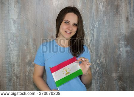 A Young Smiling Woman With A Tajikistan Flag In Her Hand. Immigration And The Study Of Foreign Langu