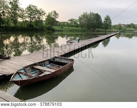Wooden Boat On The Pier On The Background Of The Lake. Fishing Boat On The Shore Of A Forest Reservo
