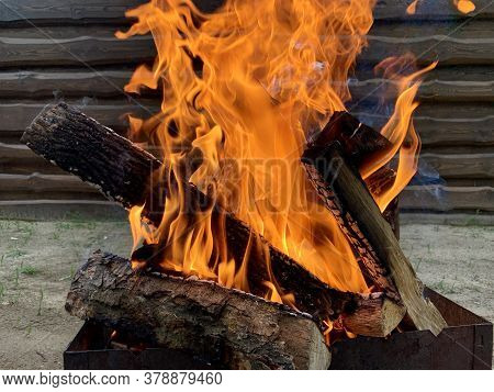 The Fire Is Burning On The Grill, Close-up. Flame Of Fire From Chopped Wood. Red Tongues Of Fire On