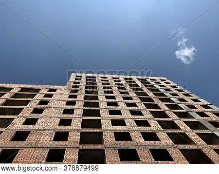 Multi-storey Building Against The Blue Sky. Tall New Building With No Windows, Bottom View. Backgrou
