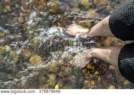 The Feet Of Men In The Wild River Stream