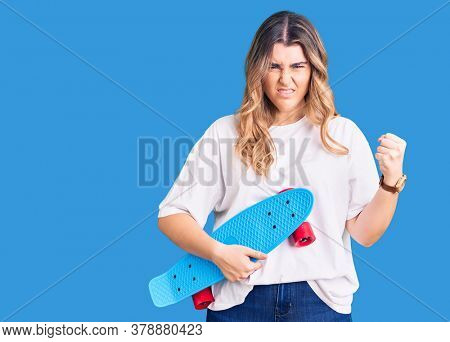 Young caucasian woman holding skate annoyed and frustrated shouting with anger, yelling crazy with anger and hand raised