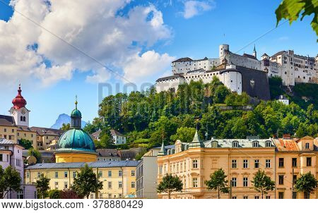 Fortress Salzburg (Festung Hohensalzburg). Austria, Salzburger Land. Medieval Castle at Cliff among summer trees under Old Town Buildings and church towers. Famous Landmark. Blue Summer Sky.