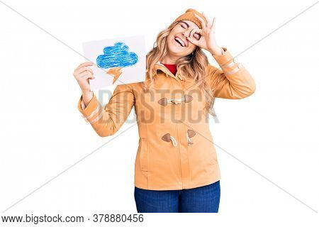Young caucasian woman holding thunder draw smiling happy doing ok sign with hand on eye looking through fingers