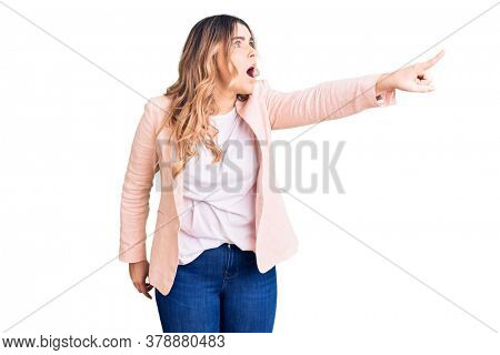 Young caucasian woman wearing business clothes pointing with finger surprised ahead, open mouth amazed expression, something on the front