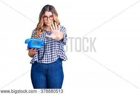 Young caucasian woman holding vintage telephone with open hand doing stop sign with serious and confident expression, defense gesture