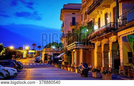 Bellagio, lake Como, Milan, Italy. Nighttime street with blue sky and lights of outdoor lanterns. Picturesque italian architecture of famous luxury Alpine health resort.