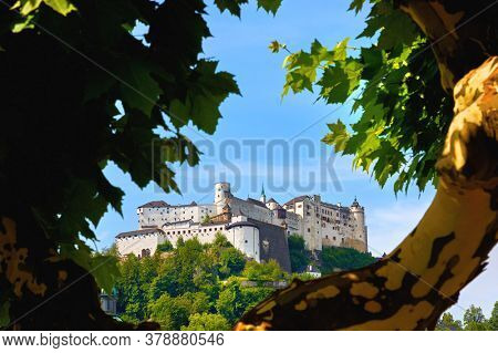 Fortress Salzburg (Festung Hohensalzburg) in Austria, Salzburger Land. Medieval Castle at Cliff among summer trees under Old Town. Famous Landmark with Blue Summer Sky with Clouds. Sunny day landmark.