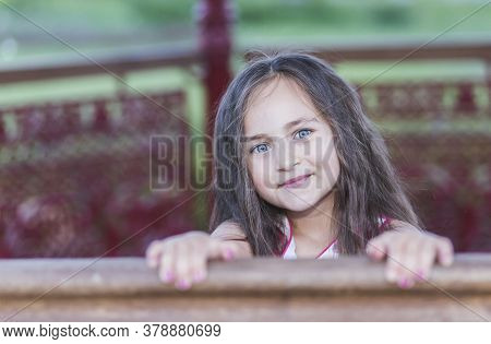 Pretty Girl In A Colorful Dress Holding Onto The Railing In The Yard