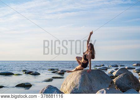 Fit female in underwear doing Camatkarasana pose on rock against cloudy sky while doing yoga exercise near sea