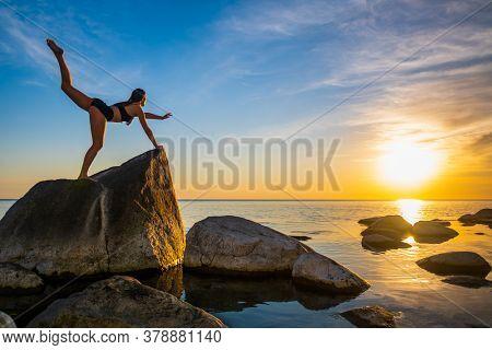Full length slim female balancing on rock in Virabhadrasana pose against sunset sky during yoga lesson near sea