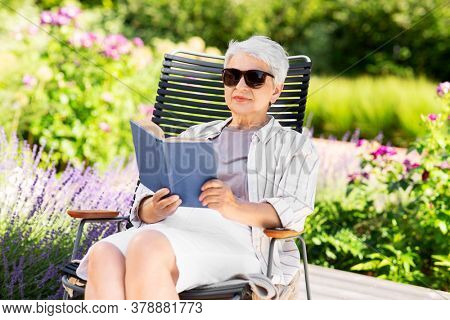 old age, retirement and people concept - happy senior woman reading book sitting in chair at summer garden