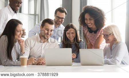 Happy Smiling Diverse Employees Using Laptop, Watching Webinar Together