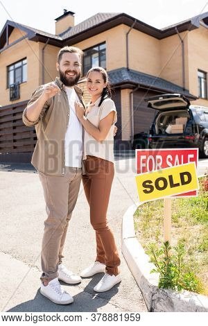 Portrait of happy beautiful young couple in casual outfits standing against new house and embracing each other while showing key from new house