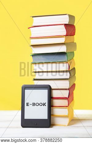 E-learning And Reading. E-book And A Stack Of Books On A Yellow Background. Vertical. Concept Of Edu